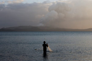 A man catches fish as the Taal Volcano continues to erupt in Talisay, Batangas, Philippines, January 14, 2020. Photo by Eloisa Lopez/Reuters