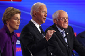 Democratic 2020 U.S. presidential candidates Senator Elizabeth Warren (D-MA) and Senator Bernie Sanders (I-VT) listen as former Vice President Joe Biden speaks during the seventh Democratic 2020 presidential debate at Drake University in Des Moines, Iowa, U.S., January 14, 2020. Photo by Shannon Stapleton/Reuters