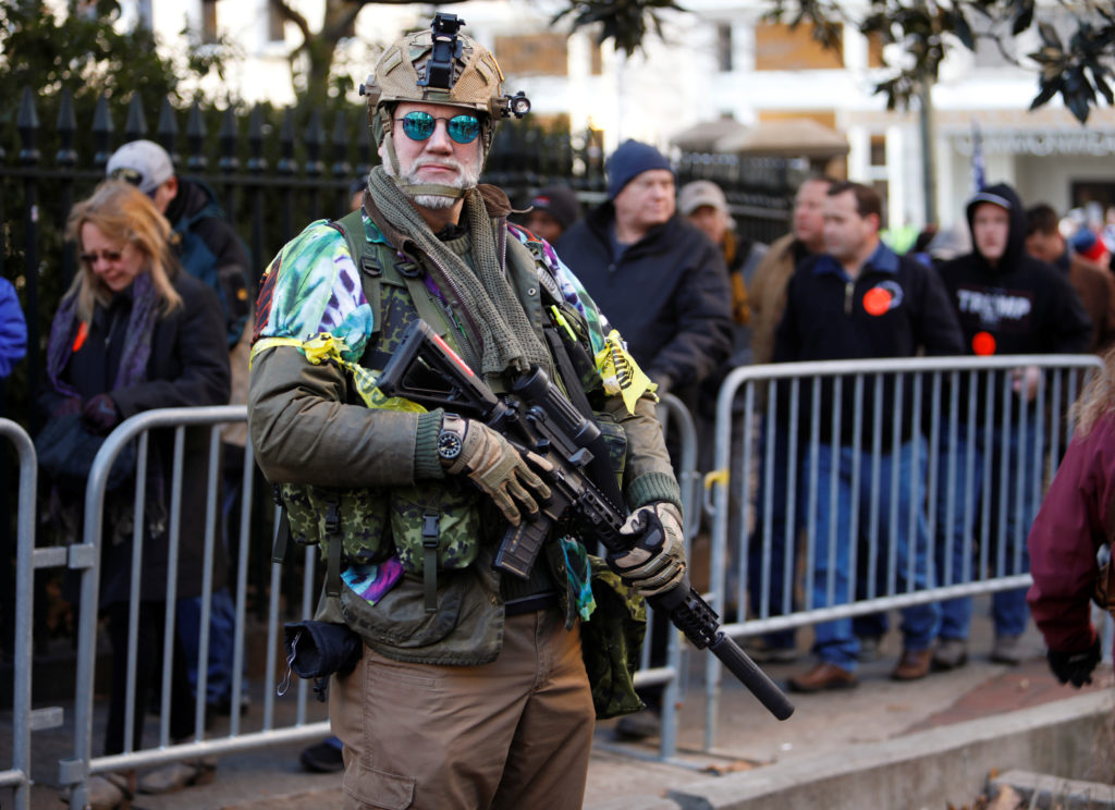 """An armed militia member stands near his """"troops"""" as others line up to enter a no-gun zone at the start of a rally by gun rights advocates and militia members near Virginia's Capitol, in Richmond, Virginia, U.S. January 20, 2020. Photo by Jonathan Drake/Reuters"""