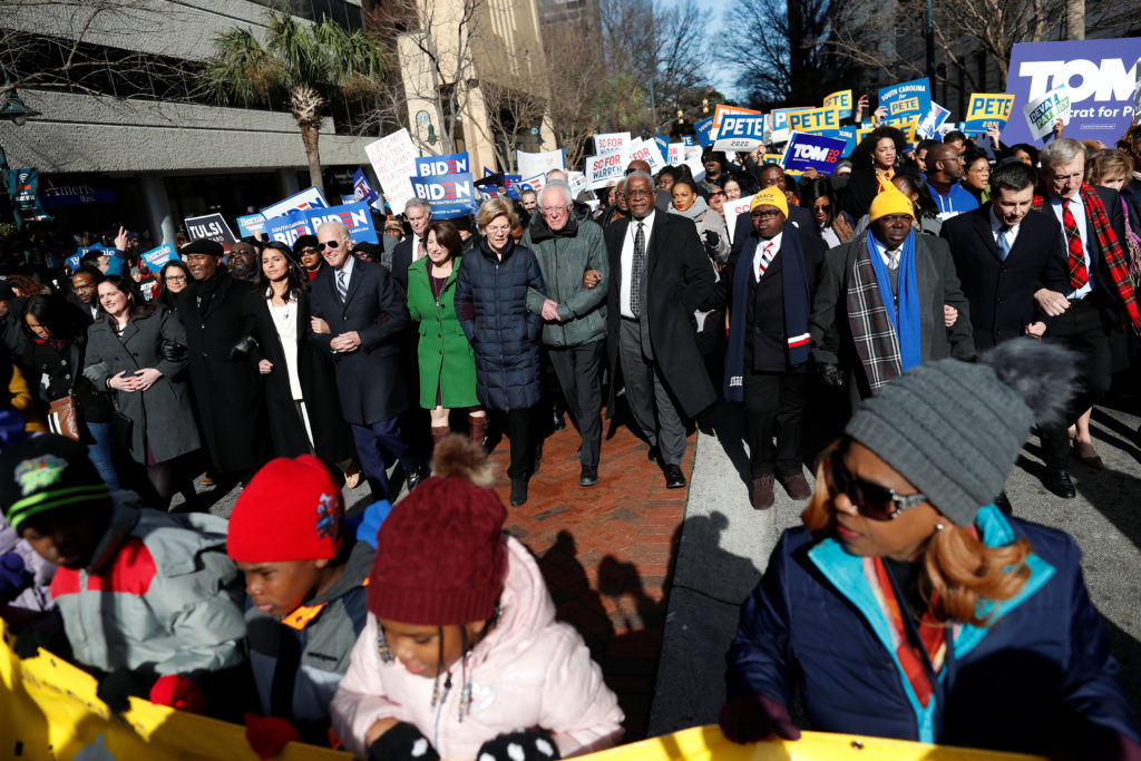 Seven of the Democratic U.S. Presidential candidates walk arm-in-arm with local African-American leaders during the Martin...