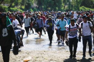 Migrants, part of a caravan travelling to the U.S., walk across the Suchiate river at the border between Guatemala and Mexico, in Ciudad Hidalgo, Mexico, January 20, 2020. Photo by Jose Cabezas/Reuters