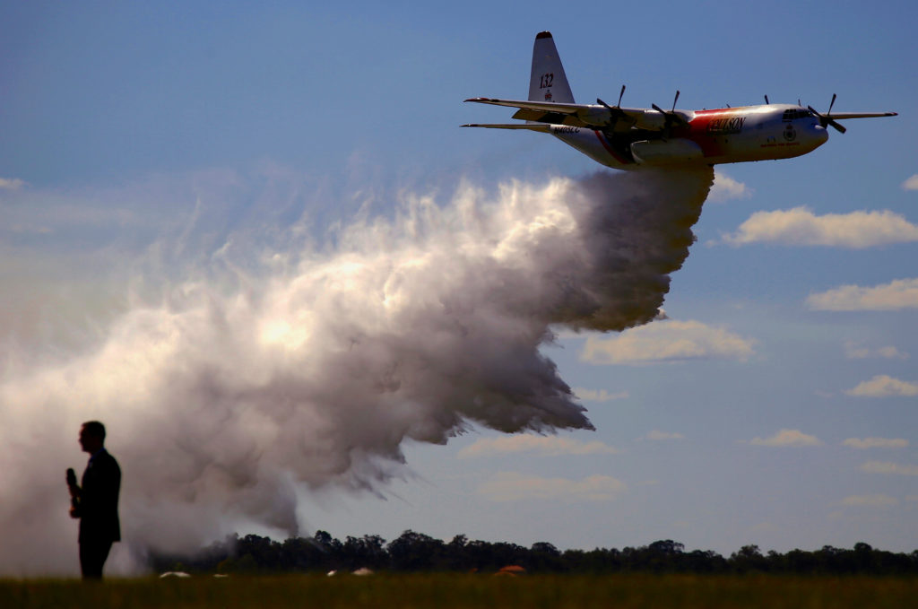 FILE PHOTO: A television reporter stands in front of a Large Air Tanker (LAT) C-130 Hercules as it drops a load of around ...