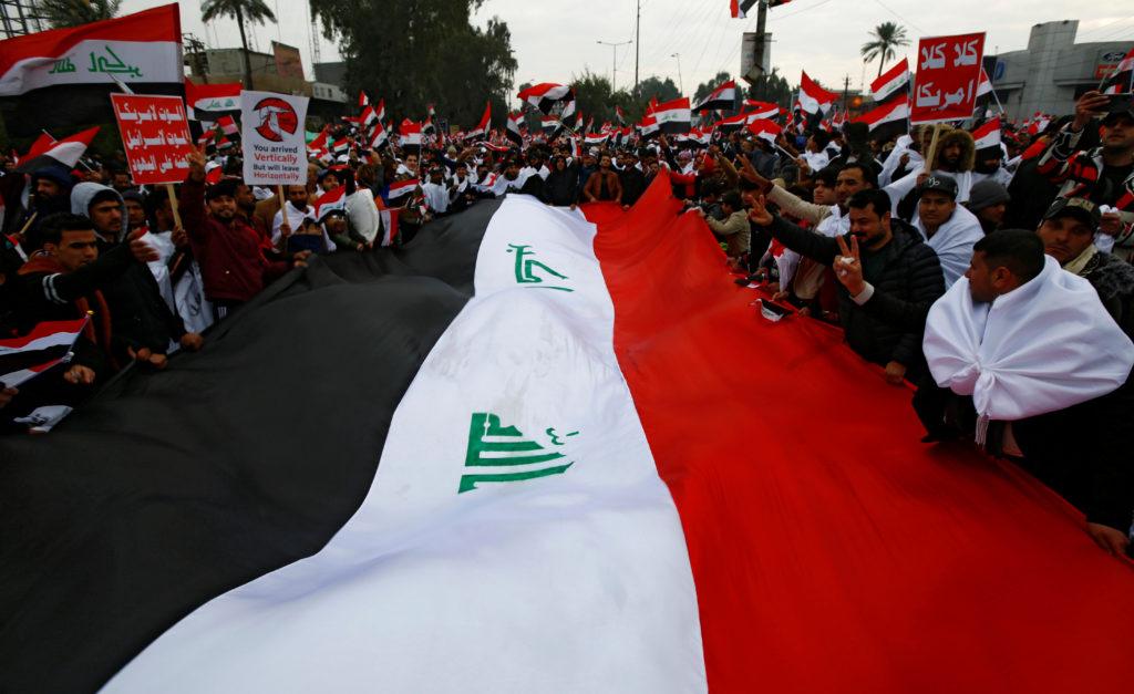 Supporters of Iraqi Shi'ite cleric Moqtada al-Sadr carry a huge Ira…