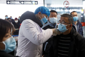 A medical official takes the body temperature of a man at the departure hall of the airport in Changsha, Hunan Province, as the country is hit by an outbreak of a new coronavirus, China, January 27, 2020. Photo by Thomas Peter/Reuters