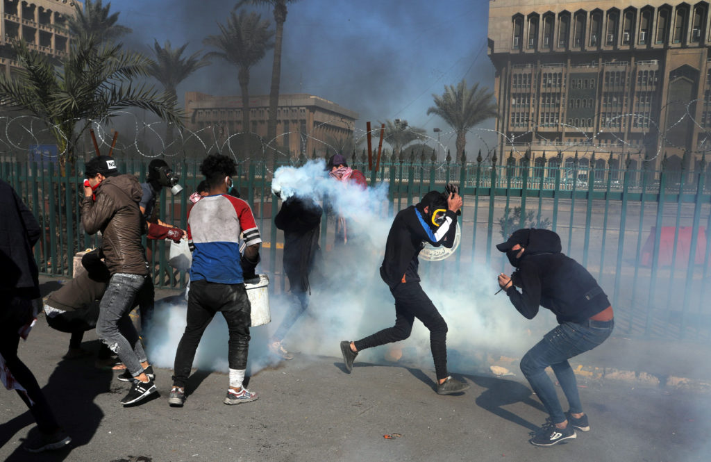 Iraqi demonstrators run from tear gas thrown during ongoing anti-government protests in Baghdad, Iraq on January 27, 2020. Photo by Abdullah Dhiaa al-Deen/Reuters