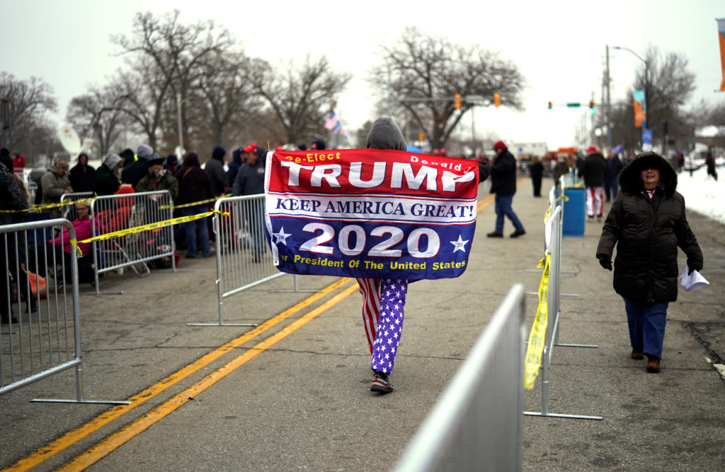 Walter Roach, a supporter of U.S. President Donald Trump, walks past people waiting in line to attend a Trump rally in Des Moines, Iowa, U.S., January 30, 2020. REUTERS/Rick Wilking
