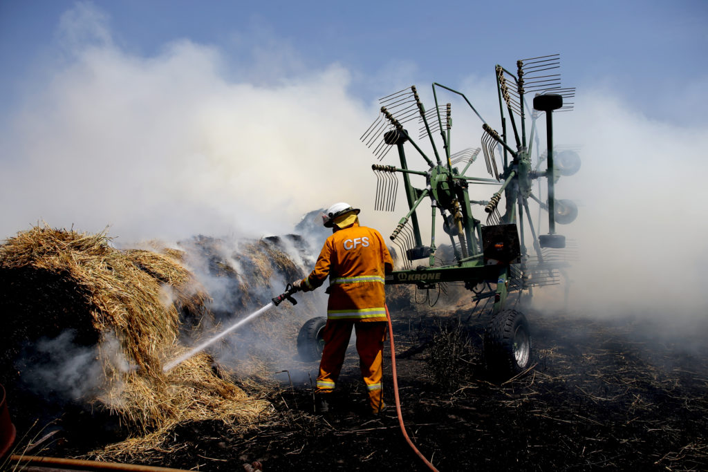Country Fire Service (CFS) members put out a fire that reached hay bales on a property at Mount Torrens in the Adelaide Hills, Australia, on January 3, 2020. Photo by Kelly Barnes/AAP, via Reuters