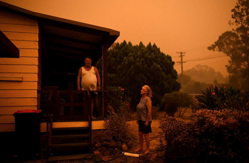 Nancy Allen and Brian Allen stand outside as high winds push smoke and ash from the Currowan Fire toward Nowra, New South ...