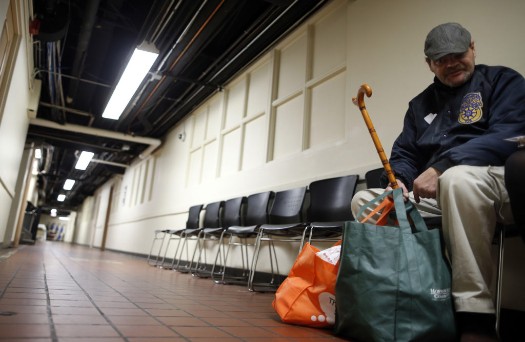 FILE PHOTO: A man sits with bags of food that were donated to him at the Emergency Assistance Program at the Chicago Catholic Charities in Chicago, November 1, 2013. Photo by Jim Young/Reuters