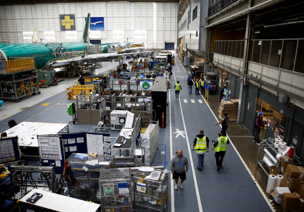 Workers walk by a 737 Max aircraft on the production line at the Bo…