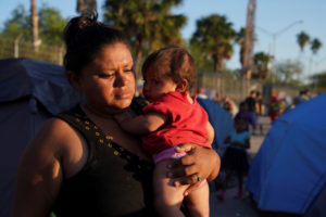 "Honduran asylum seeker Daisy V. Villalobos, 32, carries her five-month-old daughter Jimena L. Montoya in an encampment near the Gateway International Bridge where they have been living for nearly two months after being sent back under the ""Remain in Mexico"" program officially named Migrant Protection Protocols (MPP) in Matamoros, Mexico October 5, 2019. Photo by Veronica G. Cardenas/Reuters"
