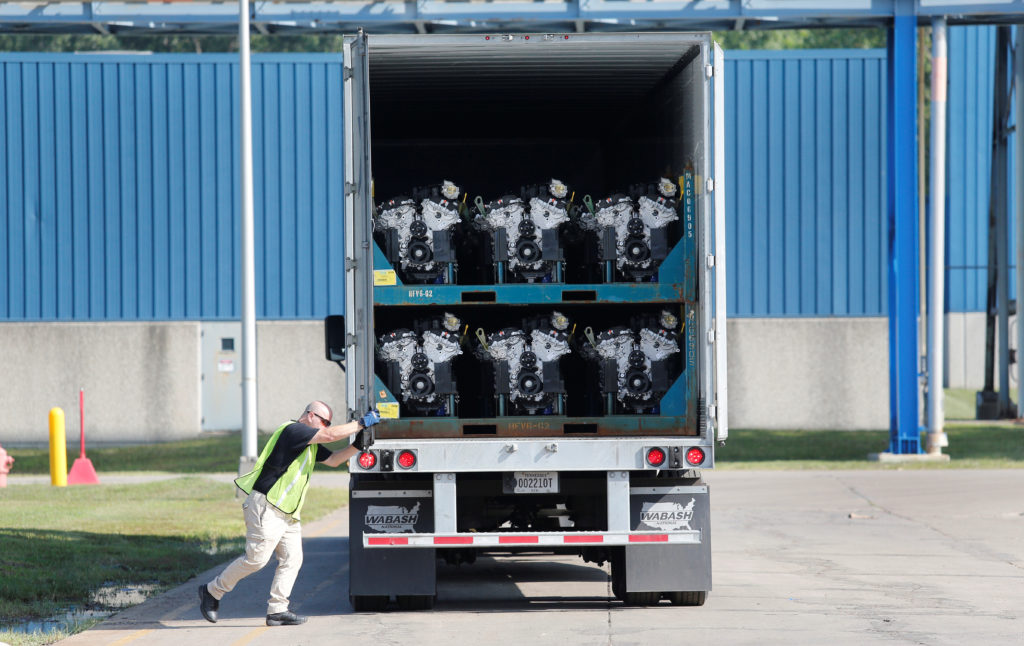 A truck driver closes the door to a transport truck loaded with V6 …