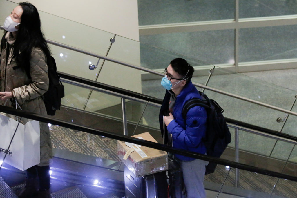 FILE PHOTO: Travelers wearing masks arrive on a direct flight from China, after a spokesman from the U.S. Centers for Dise...