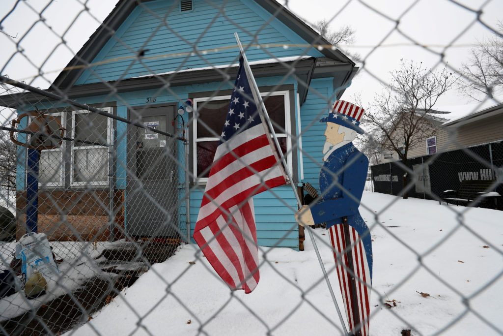 A figure of Uncle Sam holding an American flag is seen outside a ho…