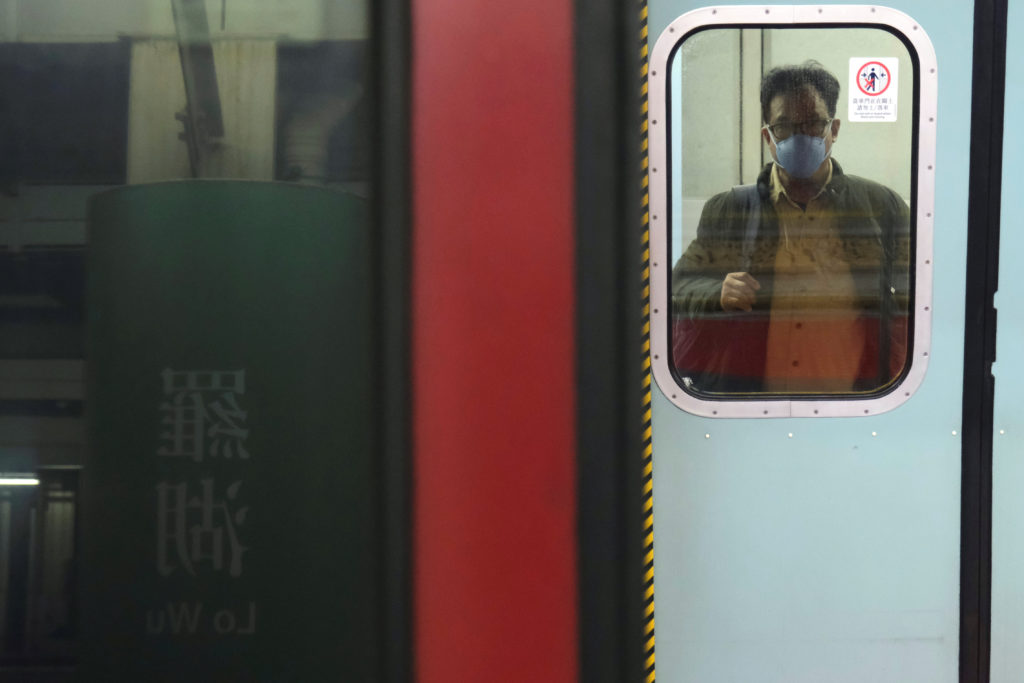 A passenger wears a face mask as he prepares to board a Hong Kong bound train at Lo Wu MTR station before the closing of t...