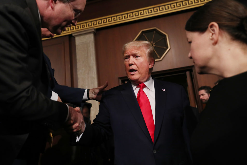 U.S. President Donald Trump is greeted by members of Congress as he arrives to deliver his State of the Union address to a...
