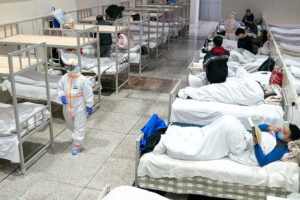 Medical workers in protective suits attend to patients at the Wuhan International Conference and Exhibition Center, which has been converted into a makeshift hospital to receive patients with mild symptoms caused by the novel coronavirus, in Wuhan, Hubei province, China February 5, 2020. Picture taken February 5, 2020. China Daily via Reuters