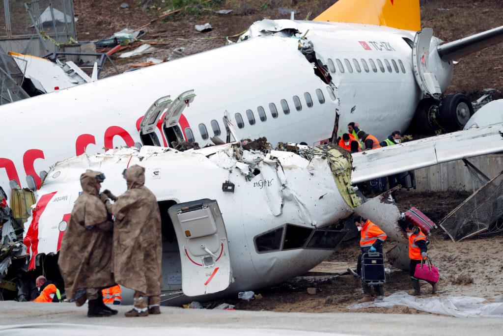 People work at the Pegasus Airlines Boeing 737-86J plane wreckage, …