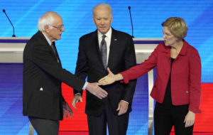 Democratic 2020 U.S. presidential candidate Senator Bernie Sanders shakes hands with Senator Elizabeth Warren as former Vice President Joe Biden looks on before the start of the eighth Democratic 2020 presidential debate at Saint Anselm College in Manchester, New Hampshire, U.S., February 7, 2020. Photo by Brian Snyder/Reuters