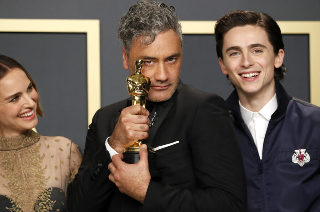 "Taika Waititi poses with the award for Best Adapted Screenplay for ""Jojo Rabbit'' with presenters Timothee Chalamet and Natalie Portman in the photo room during the 92nd Academy Awards in Hollywood, Los Angeles, California. Photo by Lucas Jackson/Reuters"