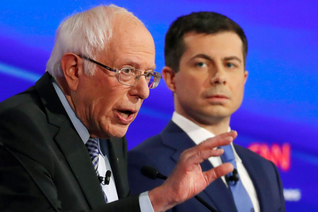 FILE PHOTO: Democratic 2020 U.S. presidential candidates (L-R) former Vice President Joe Biden listens to Senator Bernie Sanders (I-VT) as former South Bend Mayor Pete Buttigieg looks on in the seventh Democratic 2020 presidential debate at Drake University in Des Moines, Iowa, U.S., January 14, 2020. REUTERS/Shannon Stapleton/File Photo