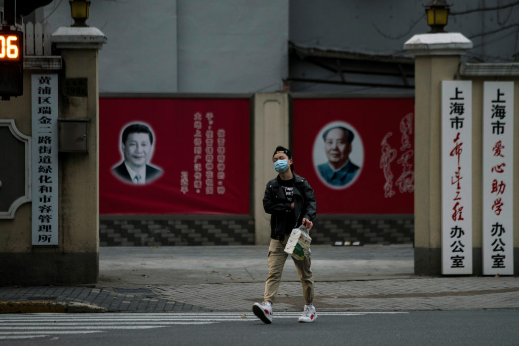 A man wearing a mask walks by portraits of Chinese President Xi Jinping and late Chinese chairman Mao Zedong as the country is hit by an outbreak of the novel coronavirus, on a street in Shanghai, China February 10, 2020. Photo by Aly Song/Reuters