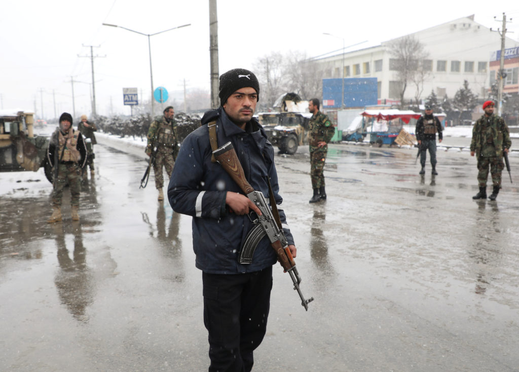 Afghan security forces keep watch near the site of a suicide attack…