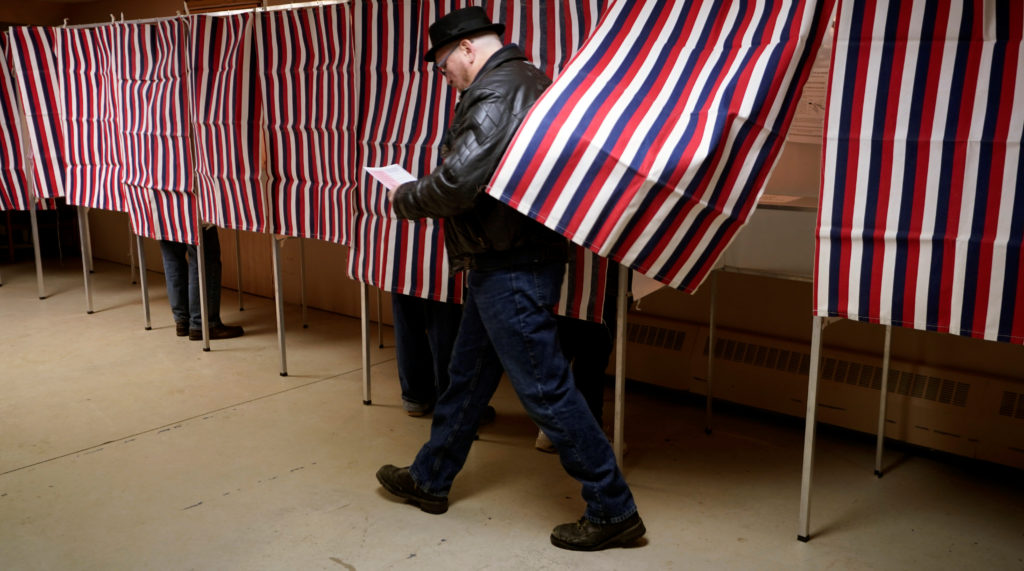 A voter leaves the voting booth at the polling place for the state's presidential primary election in Milton, New Hampshir...