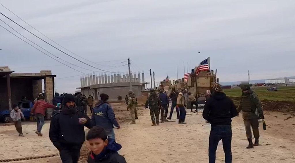People gather near U.S military vehicles in the village of Khirbet Amo, near Qamishli, Syria February 12, 2020. Photo by SANA/Handout via Reuters