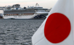 The cruise ship Diamond Princess is pictured beside a Japanese flag as it lies at anchor while workers and officers prepare to transfer passengers who tested positive for coronavirus, at Daikoku Pier Cruise Terminal in Yokohama, south of Tokyo, Japan, Feb. 12, 2020. Photo by Kim Kyung-Hoon/Reuters