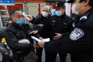 A community worker measures the body temperature of a man as police officers inspect his documents at a checkpoint set up at an entrance to a street in Wuhan, the epicentre of the novel coronavirus outbreak, Hubei province, China on February 20, 2020. China Daily via Reuters