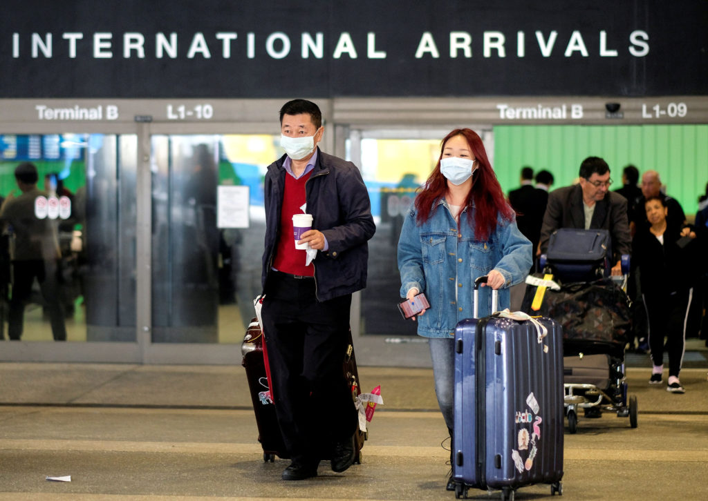 FILE PHOTO: Passengers leave LAX after arriving from Shanghai, China, after a positive case of the coronavirus was announc...