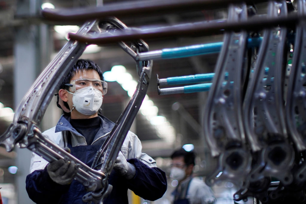 An employee wearing a face mask works on a car seat assembly line at Yanfeng Adient factory in Shanghai, China, as the cou...