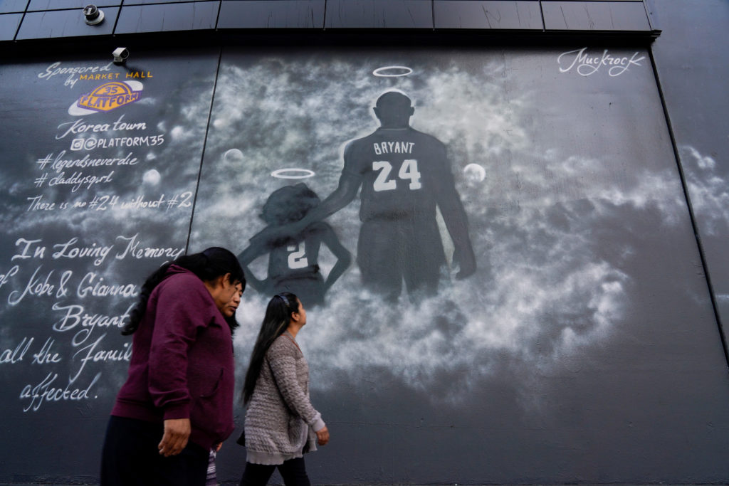 People walk past a mural before the public memorial for NBA great Kobe Bryant, his daughter and seven others killed in a h...