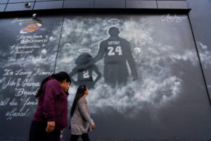 People walk past a mural before the public memorial for NBA great Kobe Bryant, his daughter and seven others killed in a helicopter crash, at the Staples Center in Los Angeles, California, U.S., February 24, 2020. Photo by Kyle Grillot/Reuters