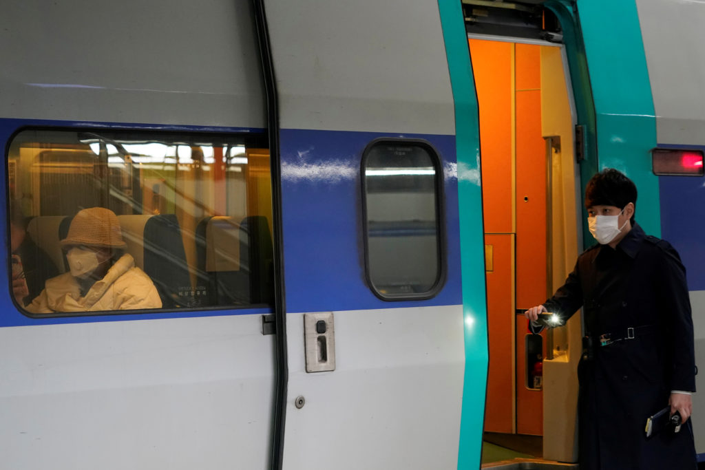 A passenger wearing a mask to prevent contacting the coronavirus sits inside a KTX train at Seoul Railway Station in Seoul...