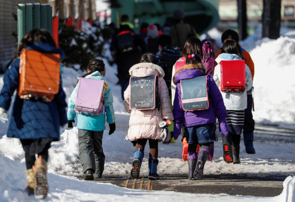 Elementary school students walk on the snow-covered street in Sapporo, Hokkaido, Japan, February 26, 2020. Photo by Issei ...
