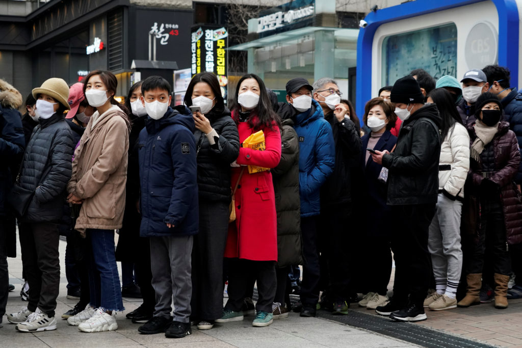 People wearing masks after the coronavirus outbreak wait in a line …