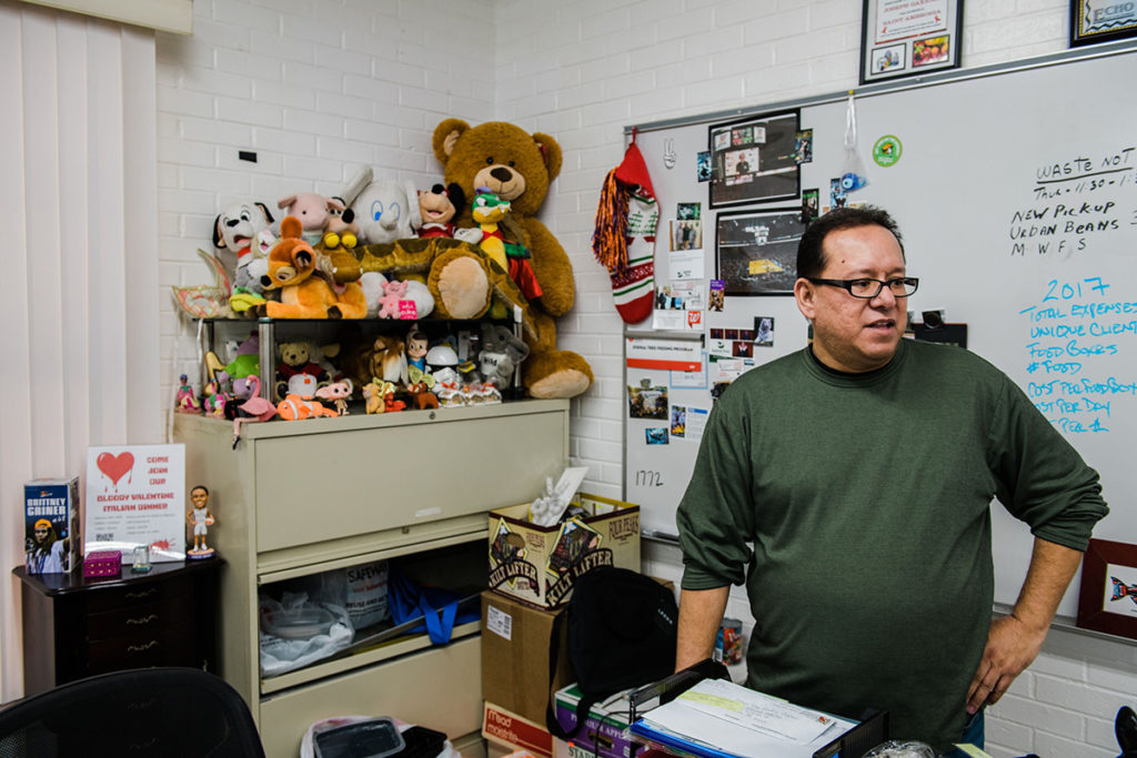 Joseph Gaxiola, who has lived with HIV for 21 years, in his office at the Joshua Tree Feeding Program — a food pantry for the HIV positive community in Phoenix — where he volunteers as chairman.  Photo Credit: Ash Ponders