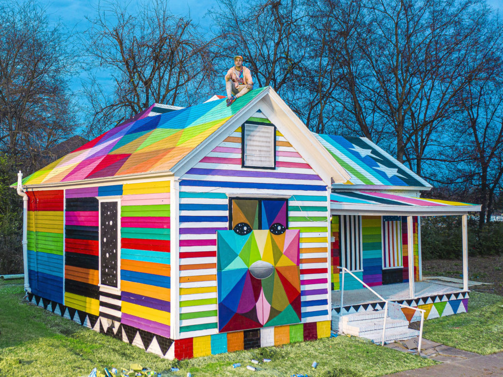 "Artist Okuda San Miguel sits atop his ""Rainbow Embassy."" Photo courtesy of Ink and Movement"