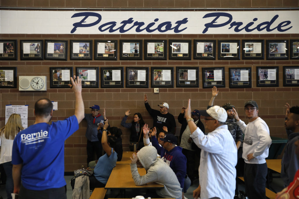 Voters supporting U.S. Democratic presidential candidate Senator Bernie Sanders raise their hands to indicate their support for Sanders during voting inside the Nevada Democratic Caucus at Liberty High School in Henderson, Nevada, U.S. February 22, 2020. REUTERS/Patrick T. Fallon - HP1EG2M1MR99D