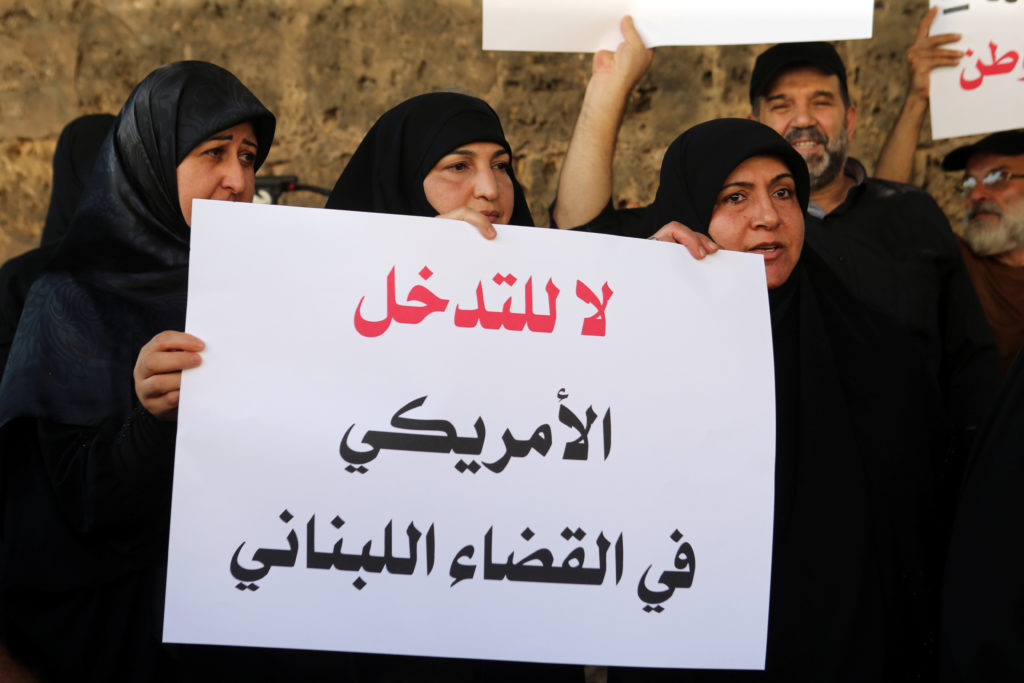 Protesters carry banners outside a military court during the hearing for Amer al-Fakhoury, in Beirut, Lebanon September 17, 2019. The banner reads 'No to the American interference in Lebanese judiciary'. Photo by REUTERS/Mohamed Azakir.