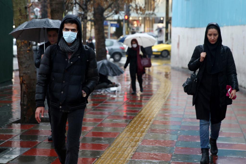 An Iranian man wears protective mask to prevent contracting coronavirus, as he walks in the street in Tehran, Iran Februar...