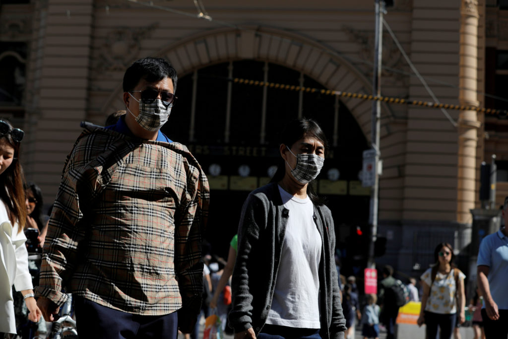 FILE PHOTO: People wearing face masks walk by Flinders Street Station after cases of the coronavirus were confirmed in Mel...