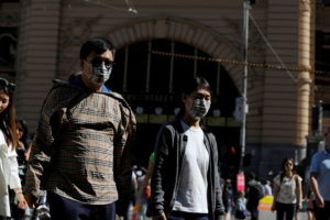 FILE PHOTO: People wearing face masks walk by Flinders Street Station after cases of the coronavirus were confirmed in Melbourne, Victoria, Australia, January 29, 2020. Photo by Andrew Kelly/Reuters