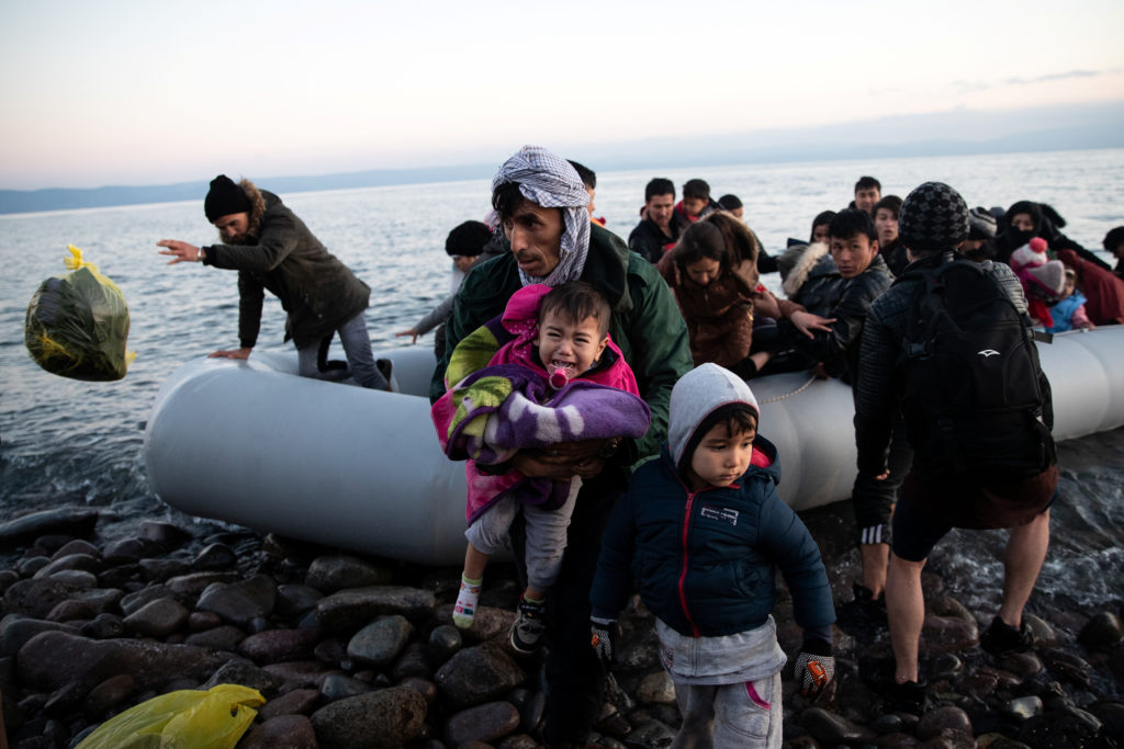 Migrants from Afghanistan arrive on a dinghy on a beach near the village of Skala Sikamias, after crossing part of the Aeg...