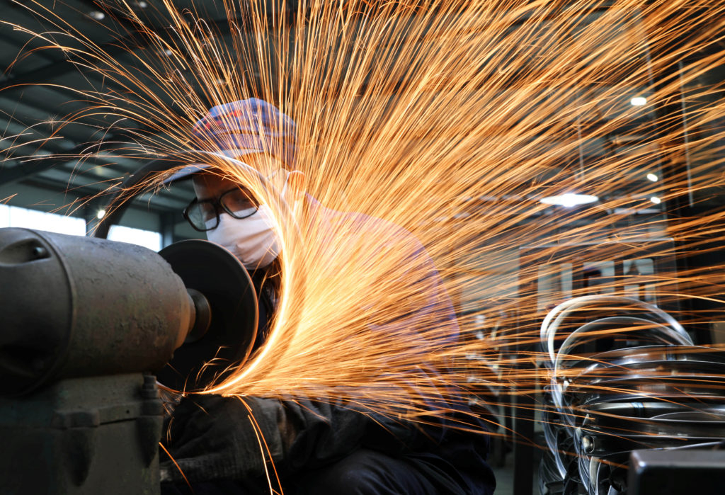 A worker wearing a face mask works on a production line manufacturing bicycle steel rim at a factory, as the country is hi...
