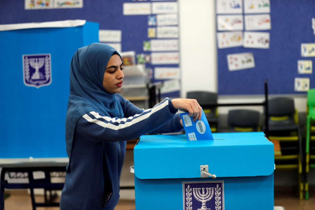 An Arab-Israeli woman casts her ballot as she votes in Israel's national election at a polling station in Tamra, Israel on...