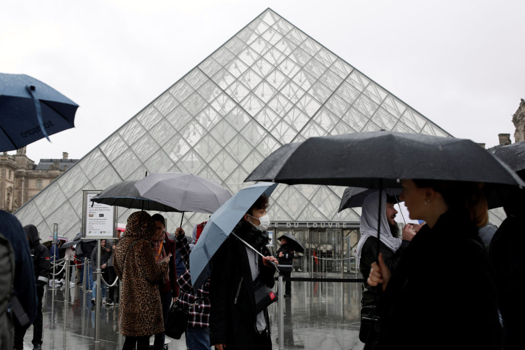 A tourist wearing a mask walks away from the Louvre as the staff closed the museum during a staff meeting about the corona...