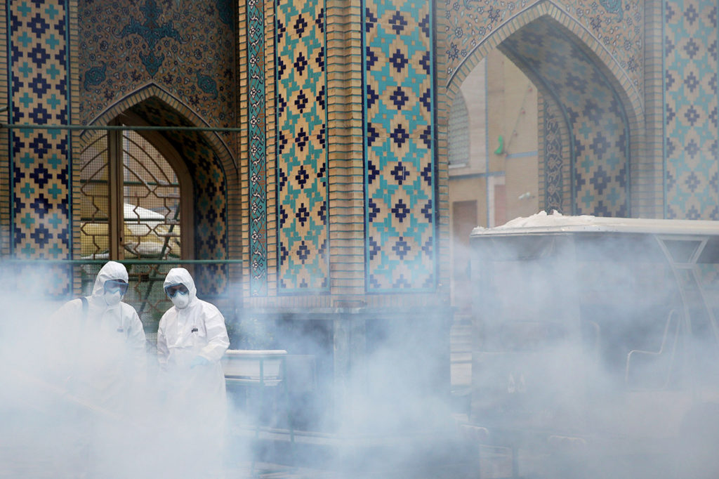 FILE PHOTO: Members of a medical team spray disinfectant to sanitize outdoor place of Imam Reza's holy shrine, following t...